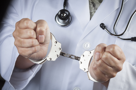 medicare: Female Doctor or Nurse In Handcuffs Wearing Lab Coat and Stethoscope.