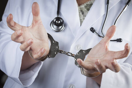 woman handcuffs: Female Doctor or Nurse In Handcuffs Wearing Lab Coat and Stethoscope.