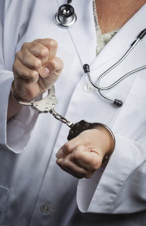 con man: Female Doctor or Nurse In Handcuffs Wearing Lab Coat and Stethoscope.
