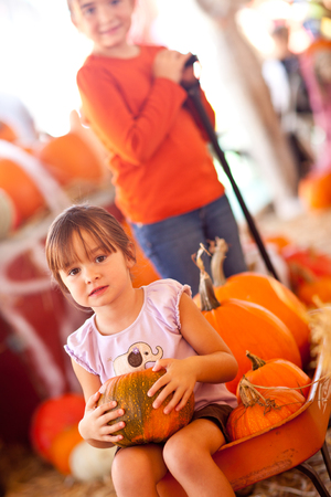 Cute Girl Riding A Wagon with Her Pumpkin and Sister At A Pumpkin Patch One Fall Day. photo