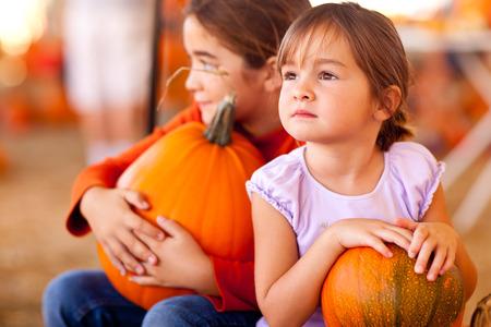 pumpkin patch: Cute Little Girls Holding Their Pumpkins At A Pumpkin Patch One Fall Day.