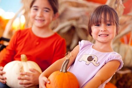 Cute Little Girls Holding Their Pumpkins At A Pumpkin Patch One Fall Day. photo
