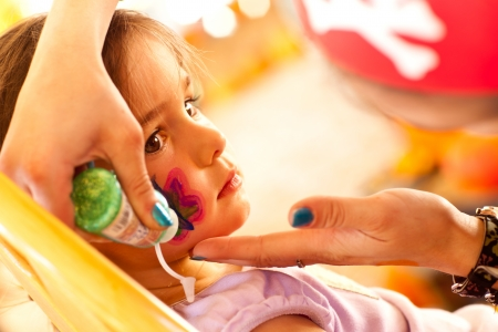Cute Little Girl Gets A Face Painting At A Party. photo