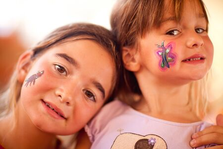 painting face: Cute Little Girls Showing Their Face Painting At A Party.