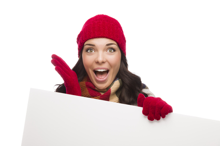 Excited Girl Wearing Winter Hat and Gloves Holds Blank Sign Isolated on White Background. photo