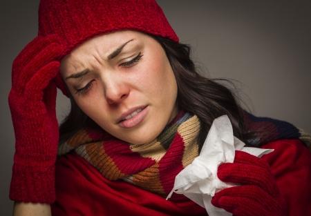 nariz roja: Sick Woman Mixed Race uso de sombrero de invierno y guantes de sonarse la nariz dolorida con un tejido. Foto de archivo