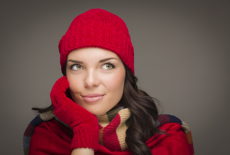 Happy Mixed Race Woman Wearing Winter Hat and Gloves Looking to the Side on Gray Background. photo