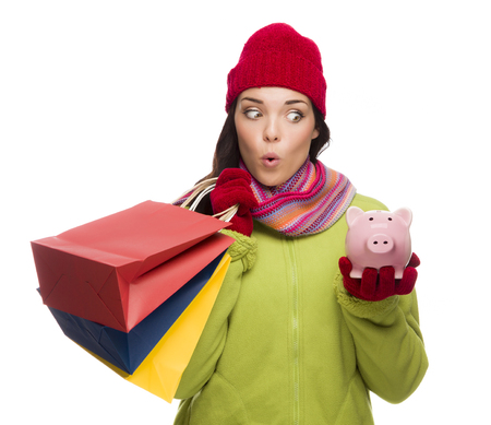christmas debt: Concerned Mixed Race Woman Wearing Winter Clothes Holding Shopping Bags and Piggybank Isolated on White Background.