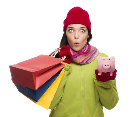 Concerned Expressive Mixed Race Woman Wearing Winter Clothes Holding Shopping Bags and Piggybank Isolated on White . photo