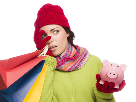christmas debt: Concerned Expressive Mixed Race Woman Wearing Winter Clothing Holding Shopping Bags and Piggybank Isolated on White .