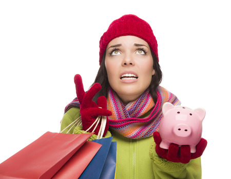 holiday spending: Stressed Mixed Race Woman Wearing Winter Clothing Looking Up Holding Shopping Bags and Piggybank Isolated on White .