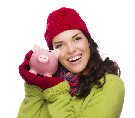 christmas debt: Happy Smiling Mixed Race Woman Wearing Winter Clothing Holding Piggybank Isolated on White .