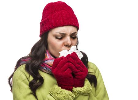 ragazza malata: Malato di sangue misto donna indossa il cappello di inverno e guanti soffiando il naso Sore con un tessuto isolato su sfondo bianco. Archivio Fotografico