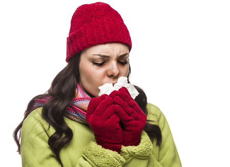 Sick Mixed Race Woman Wearing Winter Hat and Gloves Blowing Her Sore Nose with a Tissue Isolated on White Background.  photo