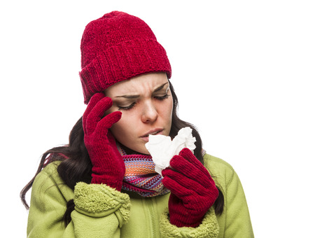 Sick Mixed Race Woman Wearing Winter Hat and Gloves Blowing Her Sore Nose with a Tissue Isolated on White Background. Stock Photo - 22812072