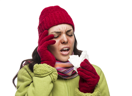 flu shot: Sick Mixed Race Woman Wearing Winter Hat and Gloves Blowing Her Sore Nose with a Tissue Isolated on White Background.
