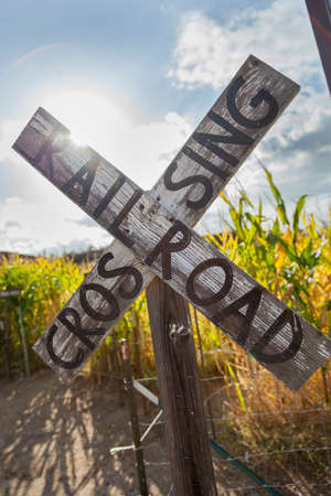 mainline: Antique Country Rail Road Crossing Sign Near a Corn Field in a Rustic Outdoor Setting.
