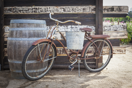 days gone by: Old Rusty Antique Bicycle and Wine Barrel in a Rustic Outdoor Setting.  Stock Photo