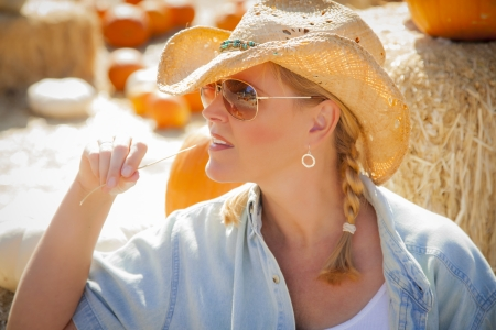 rancher: Beautiful Blond Female Rancher Wearing a Cowboy Hat in a Pumpkin Patch Chewing on a Piece of Straw.