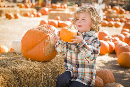 Adorable Little Boy Sitting and Holding His Pumpkin in a Rustic Ranch Setting at the Pumpkin Patch.  photo