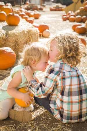 Sweet Little Boy Kisses His Baby Sister in a Rustic Ranch Setting at the Pumpkin Patch.  photo