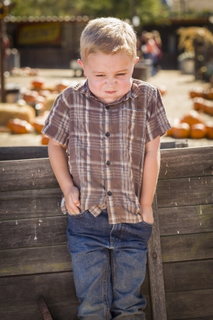 old wood farm wagon: Frustrated Little Boy at Pumpkin Patch Farm Standing Against Old Wood Wagon.  Stock Photo