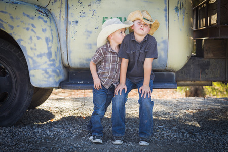 junk yard: Two Young Boys Wearing Cowboy Hats Leaning Against an Antique Truck in a Rustic Country Setting.  Stock Photo