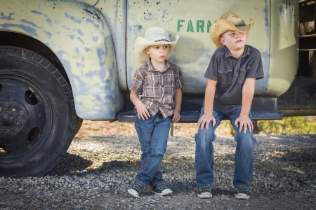 Two Young Boys Wearing Cowboy Hats Leaning Against an Antique Truck in a Rustic Country Setting.  Stock Photo