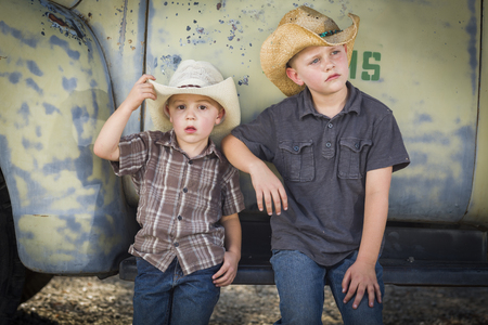 cowboy hat: Two Young Boys Wearing Cowboy Hats Leaning Against an Antique Truck in a Rustic Country Setting.  Stock Photo