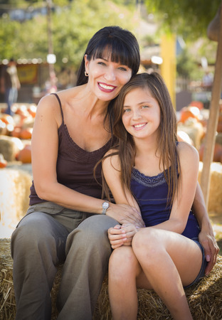 country girls: Attractive Mother and Baby Daughter Portrait in a Rustic Ranch Setting at the Pumpkin Patch.