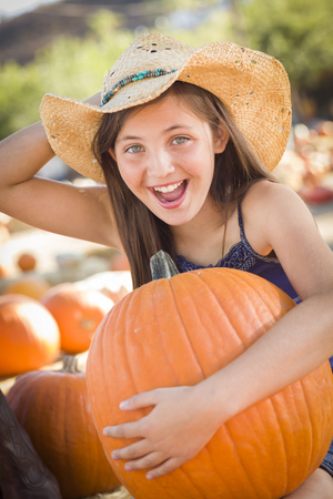 pumpkin patch: Preteen Girl Holding A Large Pumpkin at the Pumpkin Patch in a Rustic Setting.