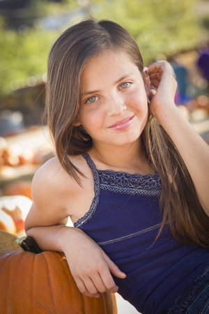 preteen girl: Preteen Girl Portrait at the Pumpkin Patch in a Rustic Setting. Stock Photo