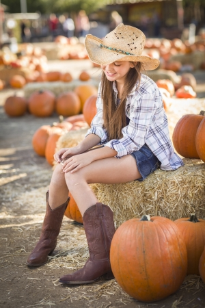 wheel barrel: Preteen Girl Wearing Cowboy Hat Portrait at the Pumpkin Patch in a Rustic Setting. Stock Photo