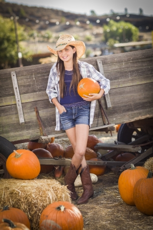 Preteen Girl Wearing Cowboy Hat Portrait at the Pumpkin Patch in a Rustic Setting. photo