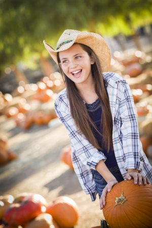 wheel barrel: Preteen Girl Wearing Cowboy Hat Playing with a Wheelbarrow at the Pumpkin Patch in a Rustic Country Setting.  Stock Photo