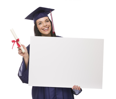 Happy Mixed Race Female Graduate in Cap and Gown Holding Blank Sign and Diploma Isolated on White. photo