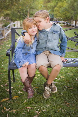 Happy Young Brother and Sister Sitting Together on a Bench Outside. photo
