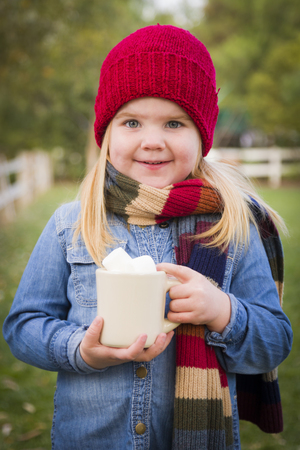 Cute Smiling Young Girl Wearing Hat and Scarf Holding Cocoa Mug with Marsh Mallows Outside.