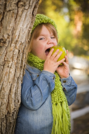 Cute Smiling Young Girl Wearing Green Scarf and Hat Eating A Green Apple Outside. photo