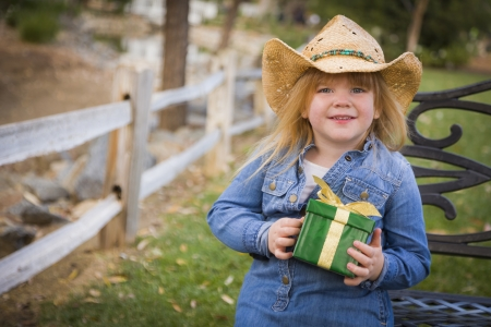 Adorable Young Girl Wearing Holiday Clothing Holding Christmas Gift Outside.