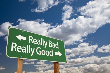 Echt slecht, echt goed Green Road Sign met dramatische wolken en lucht. Stockfoto