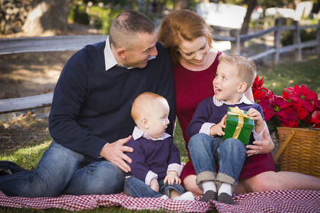 Beautiful Small Young Family Opening Christmas Gifts in the Park. photo