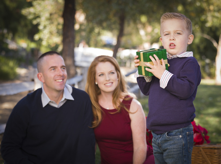 Handsome Young Boy Holding a Christmas Gift in the Park While His Mom and Dad Look On. photo