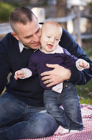Adorable Infant Boy and Young Military Father Play Together in the Park. photo