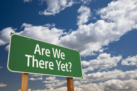green sign: Are We There Yet? Green Road Sign con cielo drammatico e nuvole. Archivio Fotografico