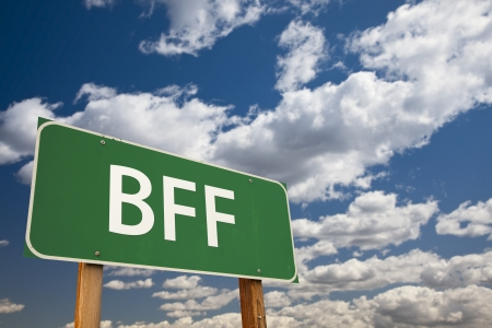 bff: BFF, Texting Abbreviation for Best Friends Forever, Green Road Sign with Dramatic Sky and Clouds.