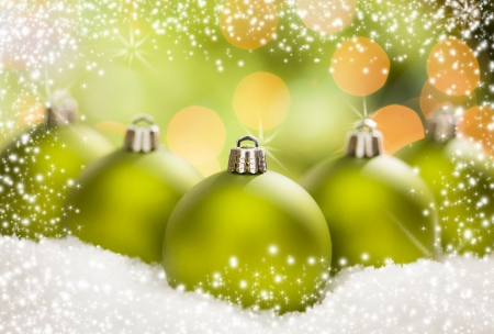 Beautiful Matt Green Christmas Ornaments on Snow Flakes Over an Abstract Snow and Light Background with Room For Your Own Text. photo