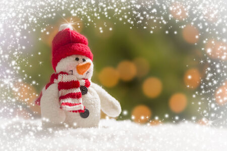 Cute Snowman Over Green and Gold Snow and Light Abstract Background. photo