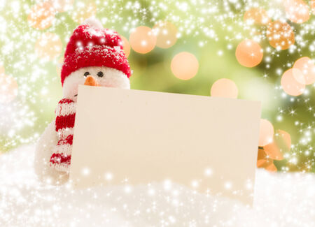 winter: Cute Snowman with Scarf and Hat Next To Blank White Card Over Abstract Snow and Light Background