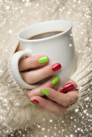 nails: Woman in Sweater with Seasonal Red and Green Nail Polish Holding a Warm Cup of Coffee with Snow Flakes Border.